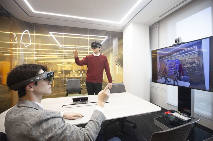 Employees at SK Telecom wearing AR glasses hold a meeting through a 'T real telepresence' system that enables those at different locations to meet together in a virtual space. / Courtesy of SK Telecom