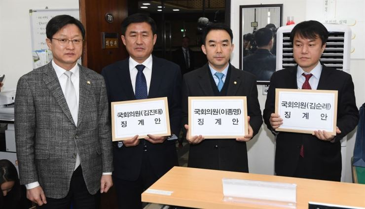 Officials of four political parties hold petitions against three Liberty Korea Party (LKP) lawmakers over their defamatory remarks against victims of the May 18 Gwangju Uprising in 1980 before submitting them to the National Assembly's Ethics Committee, Tuesday. From left are ruling Democratic Party of Korea spokesman Rep. Kang Byung-won, minor Party for Democracy and Peace spokesman Kim Jung-hyun, Rep. Chae Yi-bai of the Bareunmirae Party and Justice Party spokesman Kim Jong-chul. / Yonhap