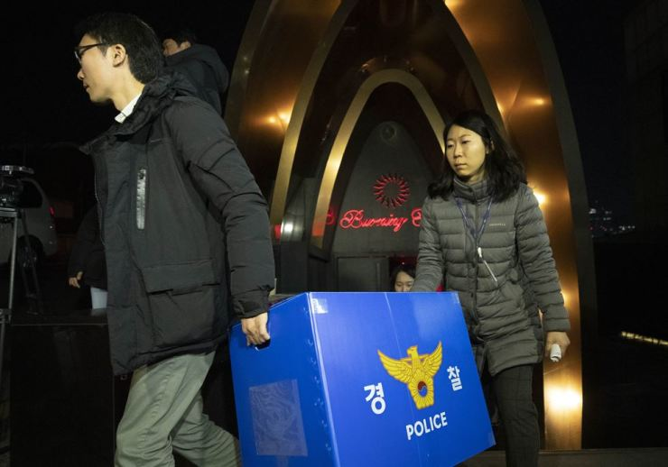 Investigators from the Seoul Metropolitan Police Agency leave Burning Sun nightclub in southern Seoul, Thursday, with materials seized in a search over drug use allegations. / Yonhap