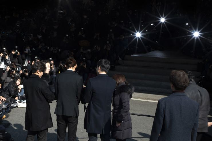 Jung Joon-young, third from left in front, charged with illegal filming and distribution of sex videos featuring himself and a variety of women, faces a mass of journalists after arriving at Seoul Metropolitan Police Agency in Jongno-gu on Thursday morning for questioning. Korea Times photo by Choi Won-suk