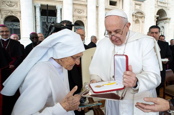 Pope Francis presents sister Maria Concetta Esu, obstetrician who was working on the mission in Africa, with the Pro Ecclesia et Pontifice medal as he holds the Wednesday general audience in Saint Peter's Square at the Vatican, March 27. Reuters