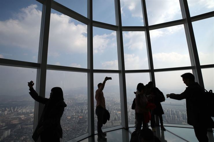 People take advantage of the clear sky to take photos of the capital from Lotte World Tower's observation deck. Yonhap