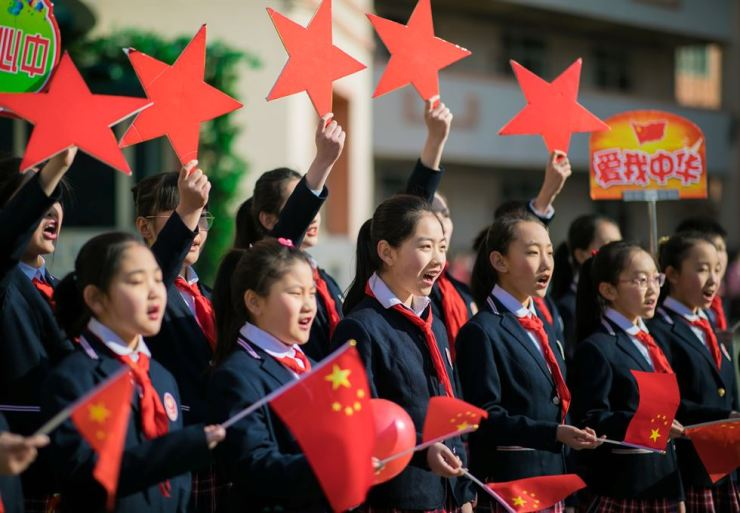 Students hold Chinese flags and cutouts of red stars as they perform a song titled 'Me and my country', at a ceremony marking the primary school's new semester in Hohhot, Inner Mongolia Autonomous Region, China February 28, 2019. Reuters-Yonhap