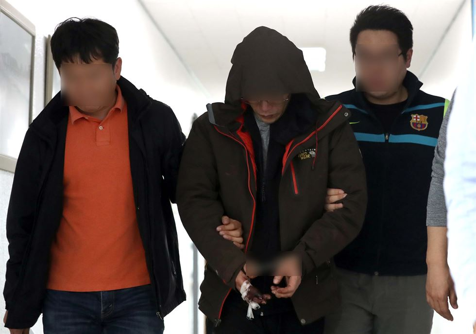 The main suspect in the killing and arson spree at an apartment building in Jinju is escorted into a police station in the South Gyeongsang Province city, Wednesday. Yonhap