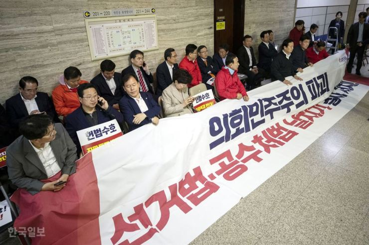 Lawmakers of the main opposition Liberty Korea Party (LKP) hold a sit-in protest in front of the office of the special committee on judiciary reform where its members will decide whether to fast-track reform bills at the National Assembly, Monday. The LKP has continued to protest the fast-track move which was agreed upon by four other political parties last week. Blocking a scheduled meeting is illegal under the Assembly Law. / Yonhap