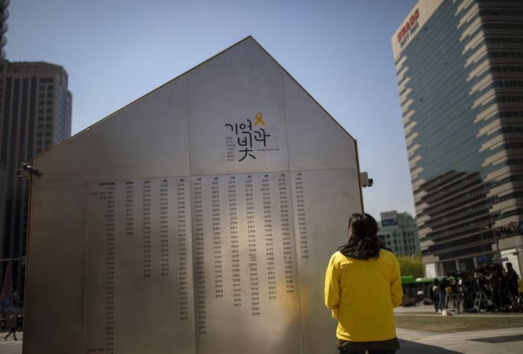 A bereaved parent of the Sewol ferry disaster scans the list of the deceased's' names on the walls of a wooden building set up at Gwanghwamun Square to commemorate the disaster victims, Monday. / Korea Times photo by Shim Hyun-chul