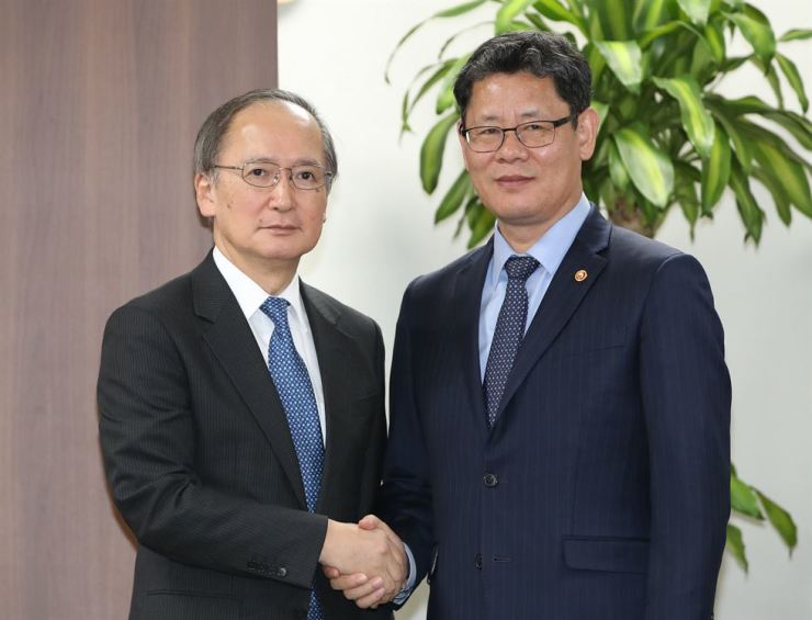 Unification Minister Kim Yeon-chul, right, shakes hands with Japanese Ambassador to South Korea Yasumasa Nagamine at the government complex in Seoul, Wednesday. Japanese semiconductor company Ferrotec Holdings has decided to shut down its business in Korea, reportedly citing South Korea's top court ruling in favor of colonial-era forced labor victims. Yonhap