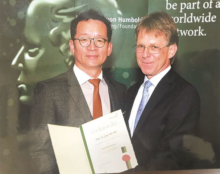 Prof. Kim Jong-bok, left, poses with Dr. Hans-Christian Pape, president of the Humboldt Foundation, after being awarded the Humboldt Research Award during a ceremony in Bamberg, Germany, Friday. Courtesy of Kyung Hee University