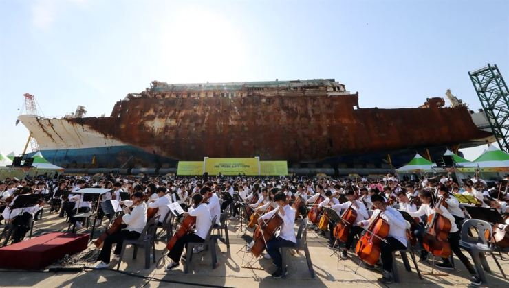 A children's band and choir perform in commemoration of the fifth anniversary of the Sewol ferry disaster at Mokpo New Port in South Jeolla Province, where the salvaged ferry now stands, Friday. / Yonhap