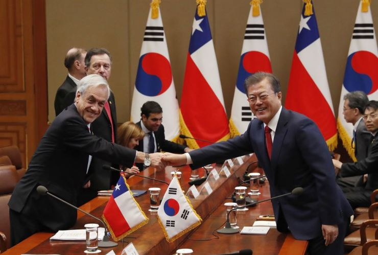 President Moon Jae-in, right and Chilean President Sebastian Pinera shake hands prior their meeting at the presidential office in Seoul, Monday. AP