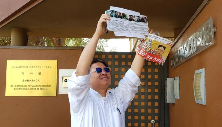 A member of Fighters for Free North, a Seoul-based human rights group focused on North Korea-related issues, tries to put up leaflets blasting North Korea's Kim Jong-un over the alleged murder of his half-brother Kim Jong-nam, at the North Korean embassy in Madrid, Spain, April 4. In late February, a group of 10 allegedly led by Adrian Hong, a longtime human rights activist, raided the embassy, according to the Spanish National High Court. Courtesy of Fighters for Free North