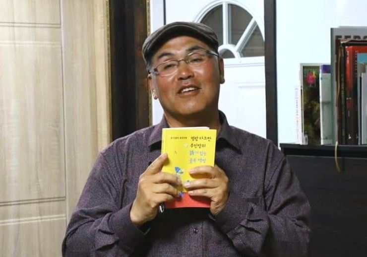 Kim Soo-hong, author of 'Sigol Books on Jeju,' poses with his book at his bookshop in Jeju's eastern town of Jocheon-ri in this undated photo. / Courtesy of Kim Soo-hong