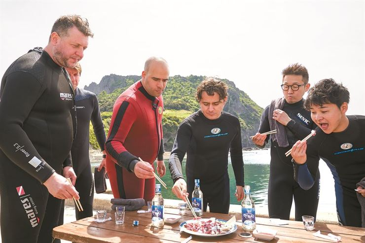 Chefs from Poland, Spain, Colombia and Japan taste raw octopus they caught in waters off Seongsan Ilchulbong Tuff Cone, Wednesday. They joined a haenyeo experience tour during the Jeju Food and Wine Festival held from Wednesday to Saturday. / Courtesy of Jeju Food and Wine Festival Organizing Committee