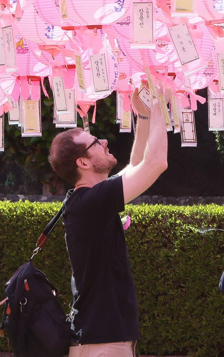 A visitor at Geungnak Temple in Aewol, Jeju Island, clips a name tag on a lantern for good luck on Sunday, Buddha's Birthday. Buddhist temples in Korea have been covered with colorful paper lanterns in the week-long celebrations leading up to this public holiday. / Yonhap