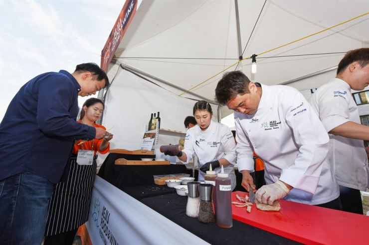 Chef Edward Kwon prepares food for customers at his booth at garden dinner, one of the programs during the Jeju Food and Wine Festival 2019, Friday./ Courtesy of Jeju Food and Wine Festival Organizing Committee