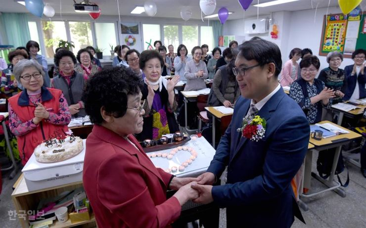 An elderly student holds hands with her teacher after pinning a carnation on his jacket at Ilsung Female Middle-High School in Mapo, Seoul, Wednesday. Korea Times photo by Suh Jae-hoon