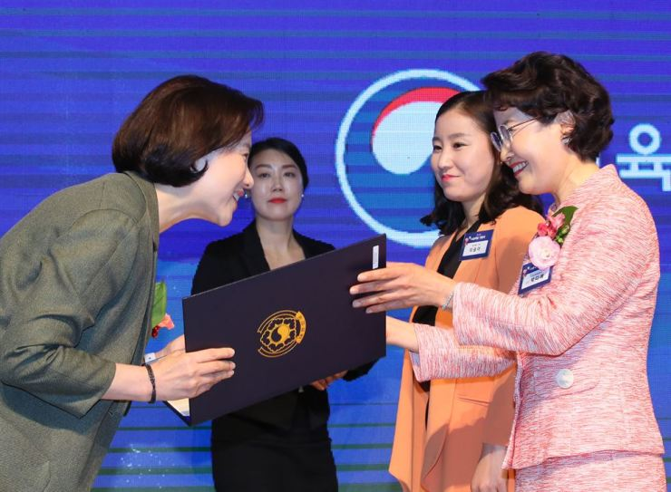 Yoo Eun-hae, left, Deputy Prime Minister and Minister of Education, hands over an order of merit certificate to Park Da-yae, principal of Sangyeok Elementary School in Daegu, during a ceremony for Teachers' Day at the government complex in Sejong City, Wednesday. Yonhap