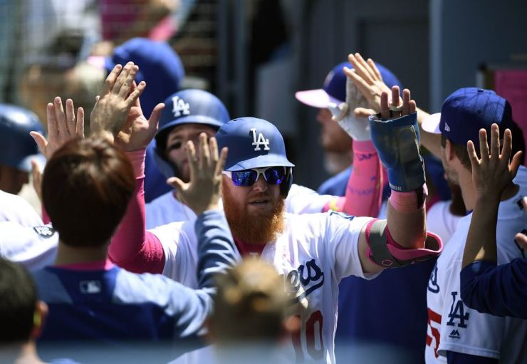 Justin Turner #10 of the Los Angeles Dodgers celebrates with teammates after scoring a run in the fourth inning against the Washington Nationals at Dodger Stadium on May 12, 2019 in Los Angeles, California. Kevork Djansezian/Getty Images/AFP