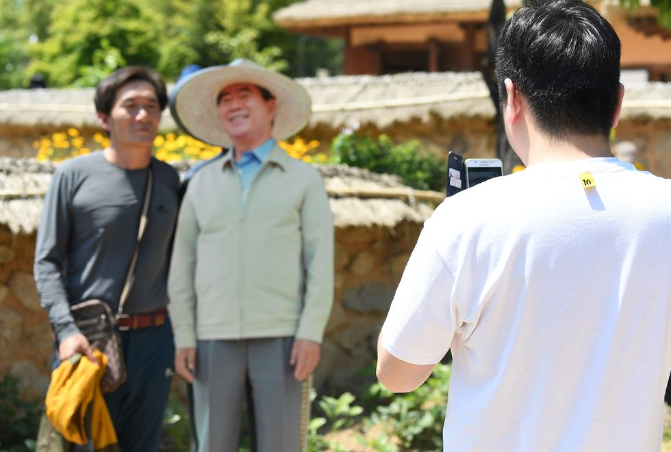 A man takes a photo of the life-size cardboard cutout of former President Roh Moo-hyun near his grave in Bongha Village in Gimhae, Thursday. Yonhap