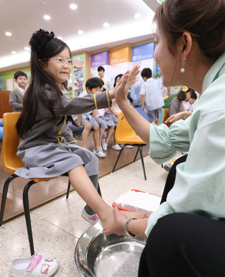 A teacher washes the foot of a student in a Teachers' Day ceremony at Youngshin Elementary School in Daegu. The school has celebrated Teachers' Day this way since 2010 to encourage teachers to have the attitude of serving students. Yonhap