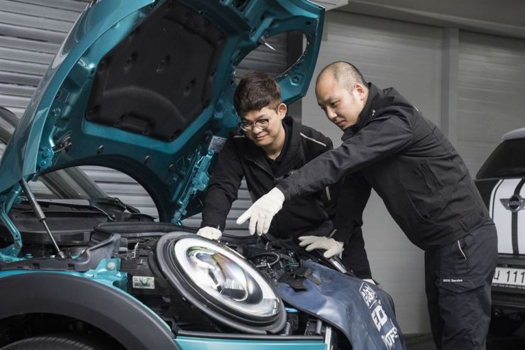 A trainee and a trainer of Korean Chamber of Commerce and Industry's (KCGGI) Ausbildung vocational training program examine a Mini vehicle at a Seoul service center of Kolon Motors, which is a dealer of BMW in Korea. Courtesy of KGCCI