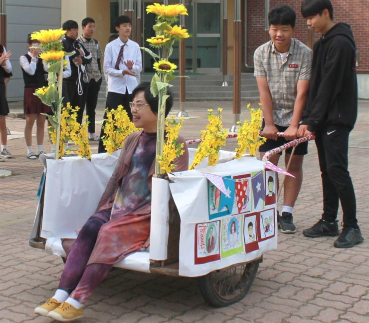 A teacher aboard a flower-decorated handcart in a ceremony for Teachers' Day at Miwon Middle School in Cheongju, Wednesday. Yonhap