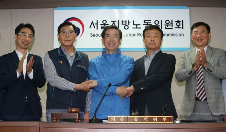 Seoul Mayor Park won-soon, center, holds hands with Seo Jong-su, second from left, head of the Seoul Bus Drivers Labor Union, and Pi Jeong-kwon, fourth from left, head of the Seoul Bus Operators Association, at the Seoul Regional Labor Relations Commission office, after reaching a deal on bus drivers' working conditions and wage hikes, Wednesday. / Yonhap