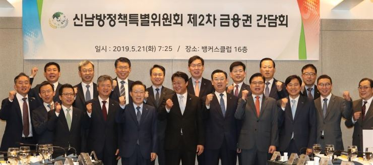 Presidential Economic Adviser Joo Hyung-chul, front row center, and Kim Tae-young, front row fifth from left, chairman of the Korea Federation of Banks, raise their fists with chief executives of financial companies ahead of their meeting in Seoul, Tuesday, to discuss expansion in Southeast Asia. Courtesy of Korea Federation of Banks