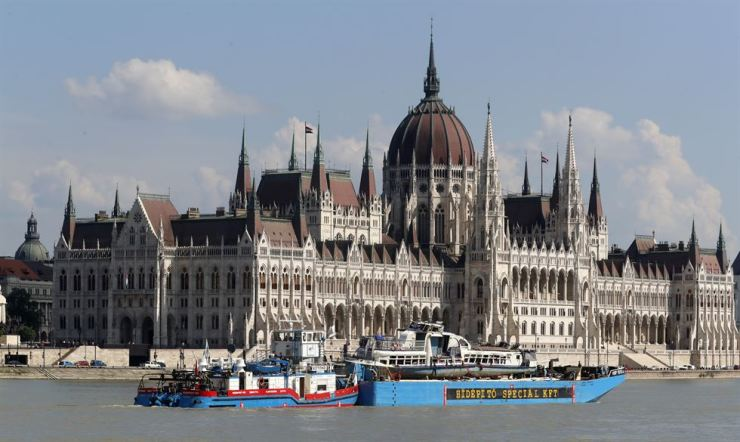 A barge carries the sightseeing boat past the house of parliament on the Danube river after it was lifted from riverbed in Budapest, Hungary, June 11. AP