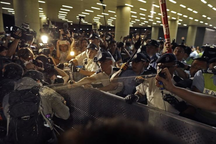 Police officers use pepper spray against protesters in a rally against the proposed amendments to the extradition law at the Legislative Council in Hong Kong during the early hours of June 10. AP-Yonhap