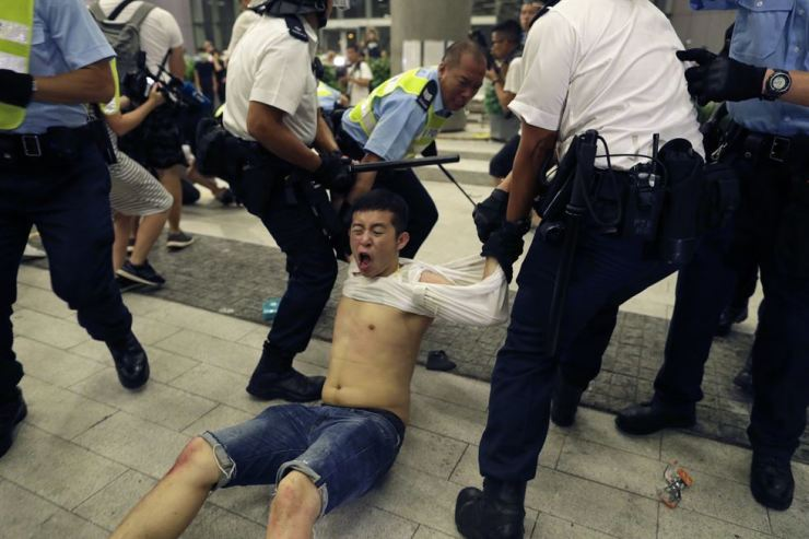 Hong Kong police officers drag away a protester during a rally against proposed amendments to the extradition law at the Legislative Council in Hong Kong during the early hours of June 10. AP-Yonhap