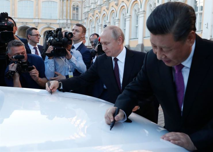 Chinese President Xi Jinping and Russian President Vladimir Putin sign autographs on a Haval F7 SUV produced at the Haval car plant located in Russia's Tula region, during a presentation at the Kremlin in Moscow, Wednesday. /AFP-Yonhap