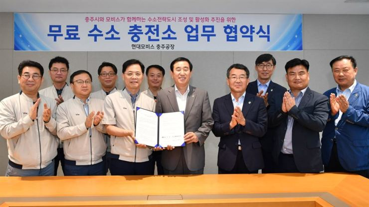 Lee Joo-gwon, head of Hyundai Mobis Chungju factory, third from left, poses with Chungju Mayor Cho Gil-hyung, after signing an agreement to open a free hydrogen refueling station for the public, Thursday. / Courtesy of Hyundai Mobis