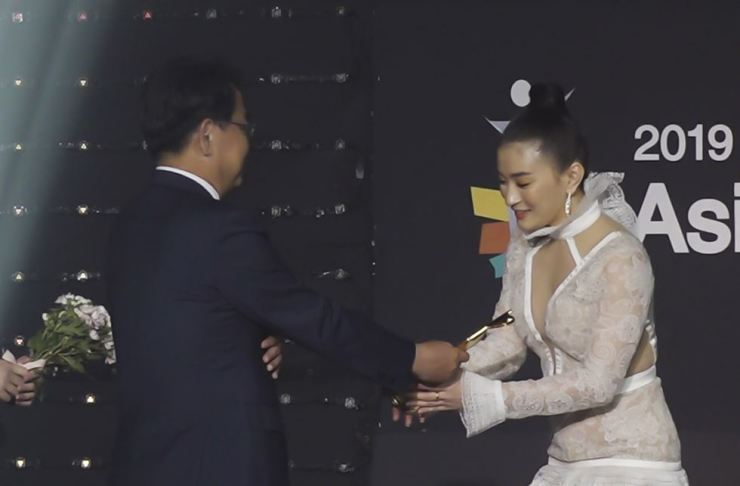 Korea Times President and Publisher Lee Byeong-eon, left, presents the Asia Special Award to Myanmar's top actress Wutt Hmone Shweyi during the 2019 Asia Model Awards ceremony at Olympic Park hall in southern Seoul, Sunday. Korea Times photo by Kim Kang-min