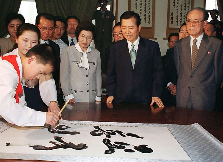 In this photo from June 14, 2000, the former South Korean President Kim Dae-jung, second from right, his wife Lee Hee-ho, third from right, and Kim Yong-nam, right, North Korean chairman of the Standing Committee of the Supreme People's Assembly, watch as a boy paints a sign which reads 'National Unification' at Mangyongdae Students' and Childrens' Palace in Pyongyang, North Korea. It was the day when the late former president began his second day of a three-day summit with North Korean leader Kim Jong-il. AP-Yonhap