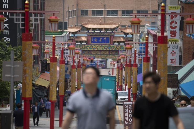 Visitors walk around streets of China Town, adorned with red and gold colors, in Incheon, Wednesday. / Korea Times photo by Choi Won-suk