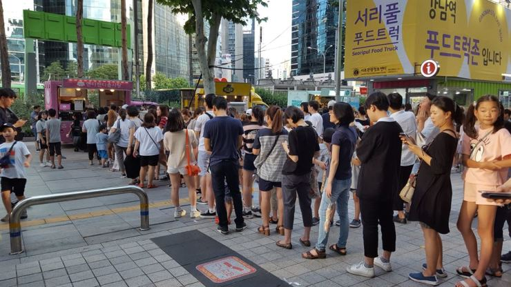 People line up to buy from food trucks at Seoripul Food Truck Zone in Seocho-gu, southern Seoul, in this September photo. Namdaemun Market will have a food truck street starting Wednesday. Courtesy of Seoul Metropolitan Government