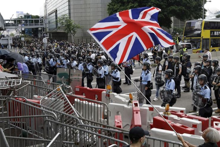 A man waves a British flag as policemen in anti-riot gear stand guard against the protesters on a closed-off road near the Legislative Council in Hong Kong, June 12. AP-Yonhap