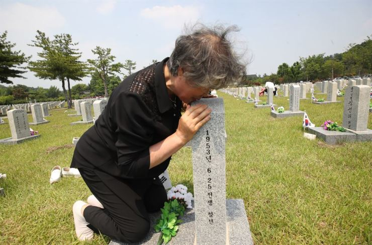 Go Hoo-gyu, 73, hugs the tombstone of his father, Go Wook-lim, killed during the Korean War, at the National Cemetery in Seoul, Monday, a day ahead of the 70th anniversary of the war's outbreak. The fratricidal war ended in a ceasefire, not a peace treaty, on July 27, 1953, leaving the two Koreas still technically at war. Yonhap
