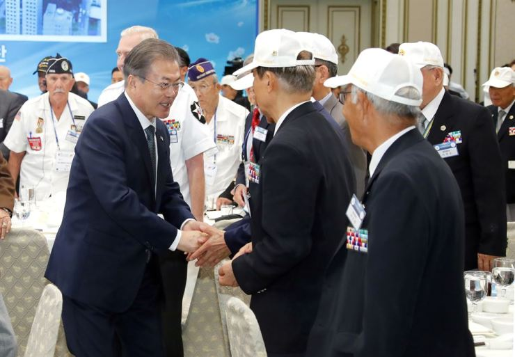 South Korean President Moon Jae-in, left, greets the Korean War veterans from South Korea, the U.S. and other countries during a luncheon prepared for them at Cheong Wa Dae, Monday. Yonhap
