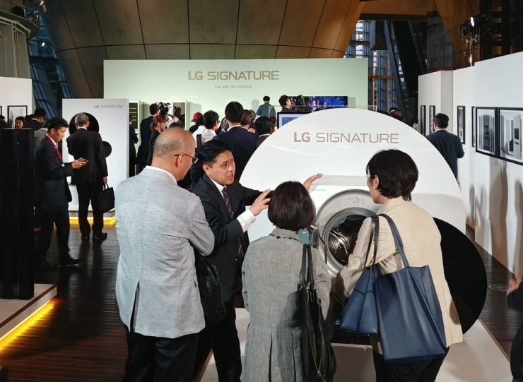 An LG Electronics employee explains the functions of the firm's dryer to visitors during a showcase event at the National Art Center in Tokyo, Tuesday.  LG전자의 한 직원이 화요일 도쿄 국립미술관에서 열린 쇼케이스 행사에서 방문자들에게 드라이어의 기능을 설명하고 있다.  /Courtesy of LG Electronics