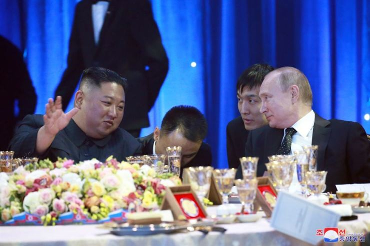 A photo released by the official North Korean Central News Agency shows North Korean leader Kim Jong-un, left, and Russian President Vladimir Putin talk during a grand banquet after Russian-North Korean talks at the Far Eastern Federal University campus on the Russky Island in Vladivostok, Russia, April 25. EPA-Yonhap
