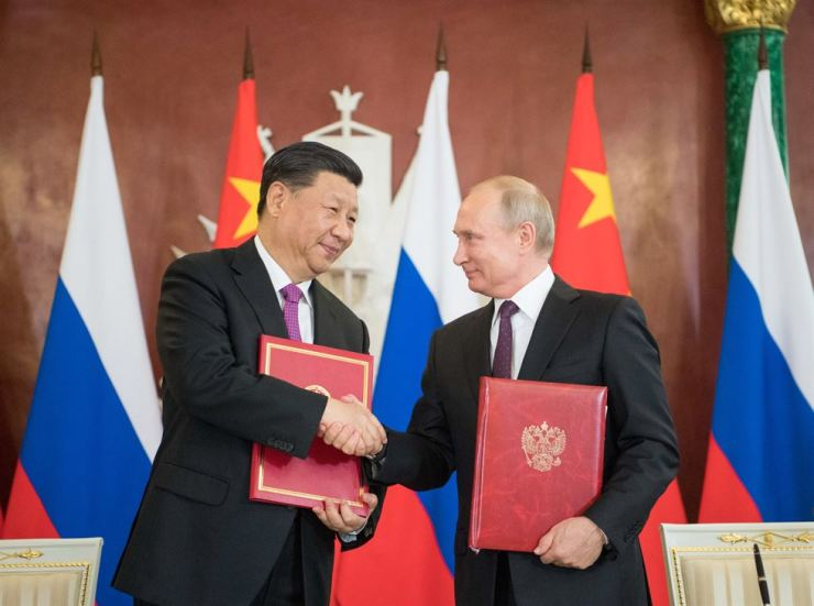 Chinese President Xi Jinping and his Russian counterpart Vladimir Putin sign the statements on elevating bilateral ties to the comprehensive strategic partnership of coordination for a new era and on strengthening contemporary global strategic stability at the Kremlin in Moscow on Wednesday.  시진핑 중국 국가주석과 블라디미르 푸틴 러시아 대통령이 수요일 모스코바 크렘린궁에서 '신시대 전면적 전략 동반자 관계'로 격상하는 내용의 공동성명에 서명하고 있다. /Xinhua-Yonhap