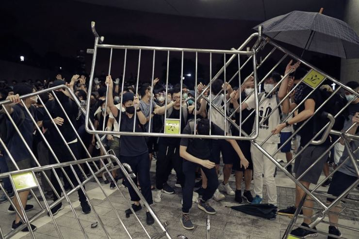 Protesters use barriers against the proposed amendments to the extradition law at the Legislative Council in Hong Kong during the early hours of June 10. AP-Yonhap