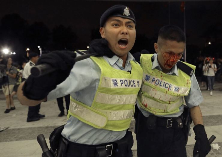 A Hong Kong police officer with blood flowing down his face is assisted by his colleague after clashing with protesters in a rally against the proposed amendments to the extradition law at the Legislative Council in Hong Kong during the early hours of June 10. AP-Yonhap