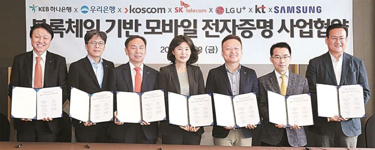 Hana Financial Group Chief Future Innovation Officer Han Jun-seong, left, and senior officials from Woori Bank, KOSCOM, SK Telecom, KT, LG UPlus and Samsung Electronics hold copies of a signed memorandum of understanding at The Plaza Seoul, Autograph Collection, July 12. Courtesy of KEB Hana Bank
