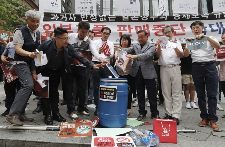 South Korean small and medium-sized business owners throw papers showing logos of major Japanese brands into a trash can during a rally calling for a boycott of Japanese products in front of the Japanese embassy in Seoul, South Korea, Monday, July 15, 2019. South Korea and Japan last Friday, July 12, failed to immediately resolve their dispute over Japanese export restrictions that could hurt South Korean technology companies, as Seoul called for an investigation by the United Nations or another international body. The signs read: 'Our supermarket does not sell Japanese products.' (AP Photo/Ahn Young-joon)