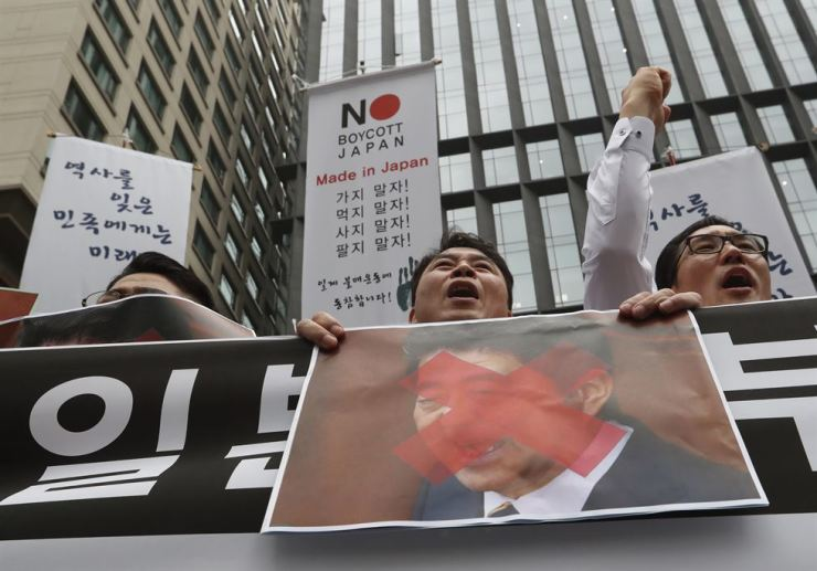 South Korean small and medium-sized business owners with a defaced image of Japanese Prime Minister Shinzo Abe shout slogans during a rally calling for boycott of Japanese products in front of the Japanese embassy in Seoul, South Korea, Monday, July 15, 2019. South Korea and Japan last Friday, July 12, failed to immediately resolve their dispute over Japanese export restrictions that could hurt South Korean technology companies, as Seoul called for an investigation by the United Nations or another international body. The signs read: 'We don't sell Japanese products.' (AP Photo/Ahn Young-joon)