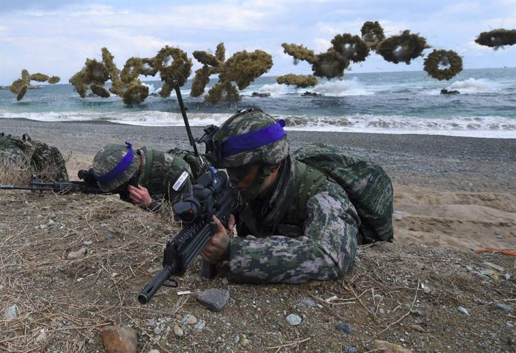 In this file photo taken on April 02, 2017 South Korean Marines take position on a beach as amphibious assault vehicles fire smoke shells during a joint landing operation by the U.S. and South Korean Marines in the southeastern port of Pohang. AFP-Yonhap