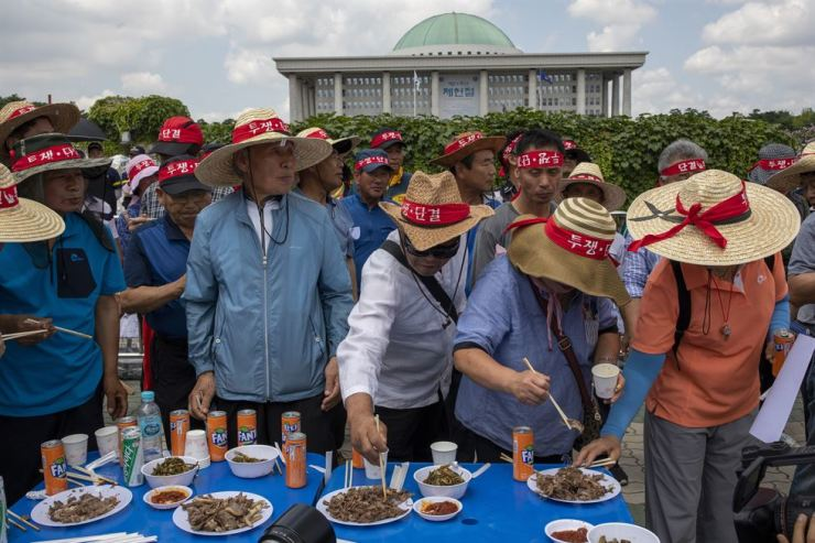 Dog meat farmers hold a tasting event next to an animal rights groups' rally. / Korea Times photo by Shim Hyun-chul
